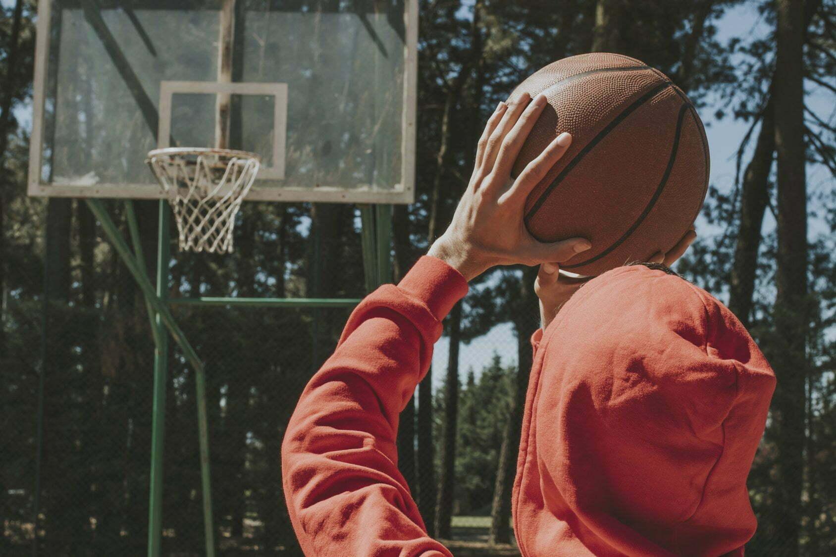 young man with basketball ball throwing basket
