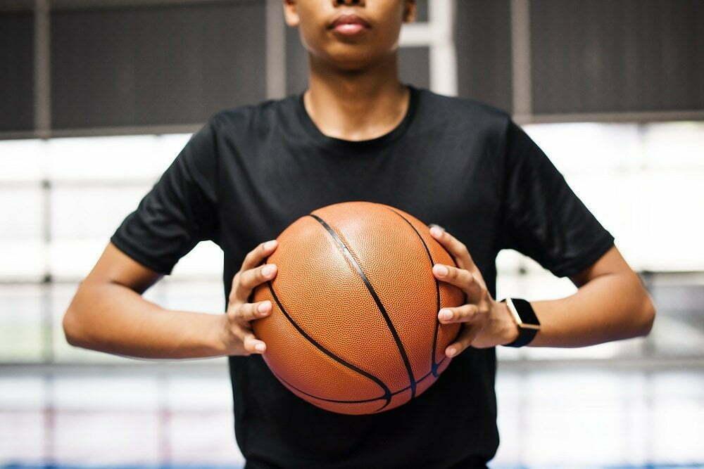 African American teenage boy holding a basketball